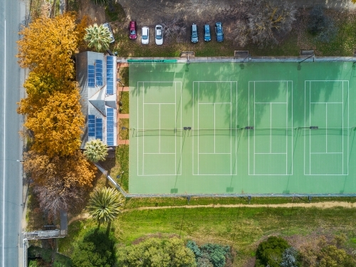 Aerial view of tennis courts with solar panels on the roof of the clubrooms and Autumn trees