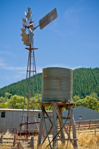 A water tank and windmill standing near farm sheds