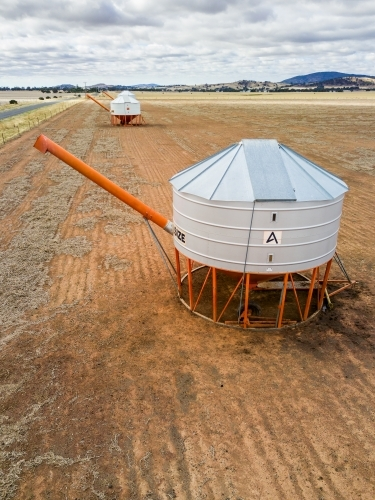 An aerial view of grain bins in a paddock