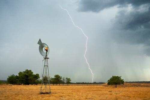 Lightning strikes ahead of a thunderstorm on farmland