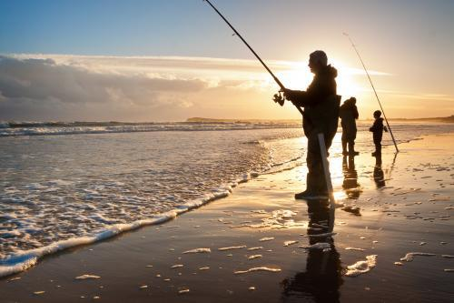 Fishermen on the beach at sunset