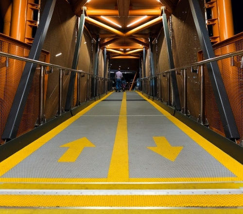view along an enclosed walkway to a person with yellow lines and arrows