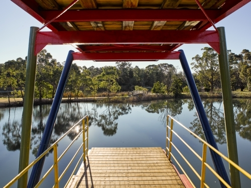 view looking out from a two-tiered diving platform onto a lake