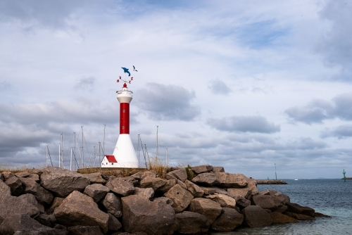 View of a miniature lighthouse on a rocky groyne with dramatic sky and harbour