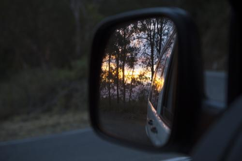 View of a sunset in a car mirror