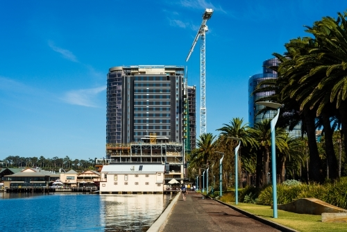 View of buildings and large crane from pathway beside water