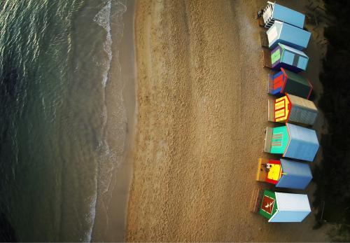 View of colourful beach boxes and ocean from above