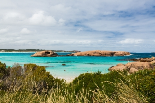 View of cove with turquoise water and colourful rocky islands and shrubs in the foreground.