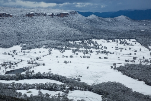 View of snow-covered paddocks and forested escarpment