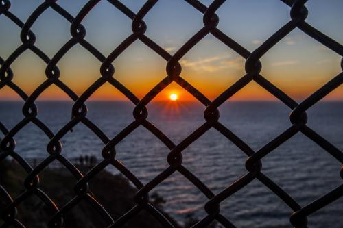 view of sunrise over the ocean through a wire fence