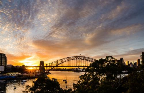 View of Sydney Harbour Bridge with  Opera House  and sun rising with colourful sky cloud patterns.