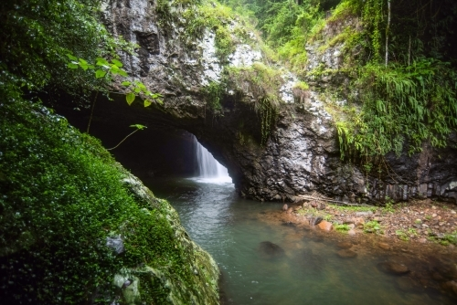 View of the waterfall through an opening of a cave mouth with the greenery surrounds
