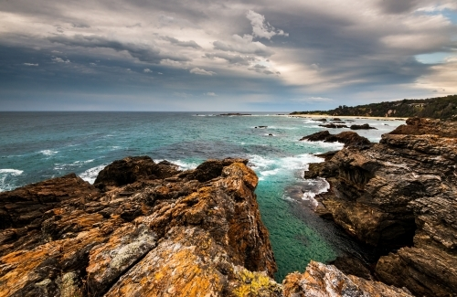View over Mystery Bay with dramatic rocks in foreground and stormy sky