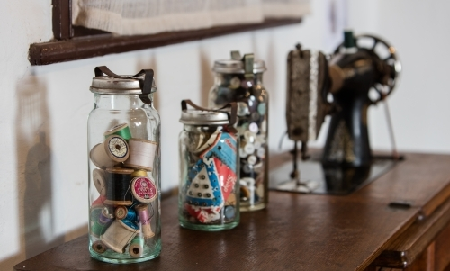 Vintage jars of sewing items with an old singer sewing machine