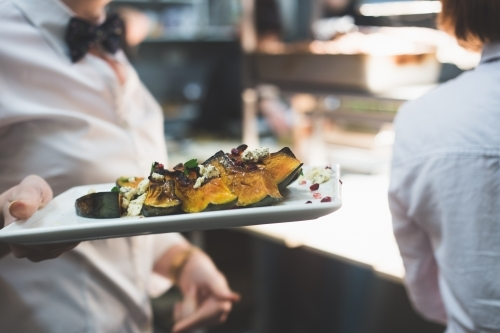 Waiter wearing a bow tie and carrying a plate of roasted pumpkin in a restaurant kitchen