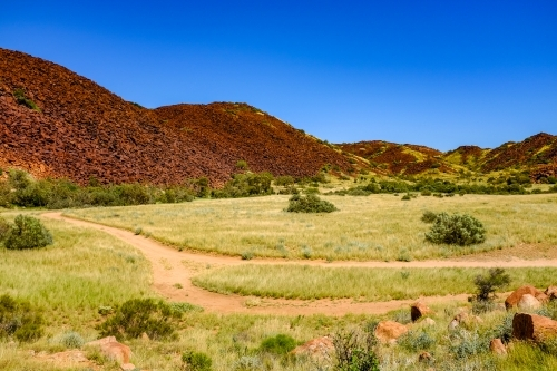Walking track and red rock mountain off Karratha beach