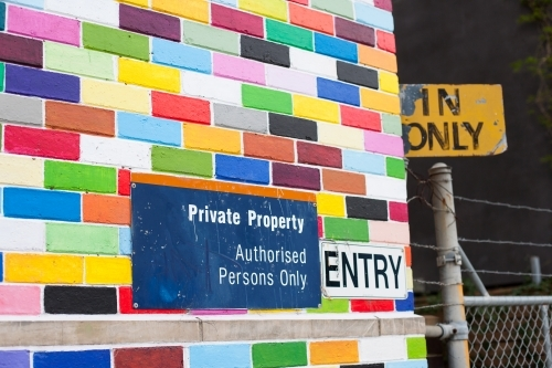 Coloured brick wall, signage and a gate on a city street