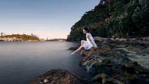 Girl peacefully relaxing by the water's edge in a white dress