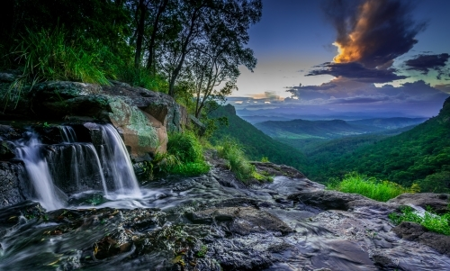 Waterfall overlooking valley of green bushland