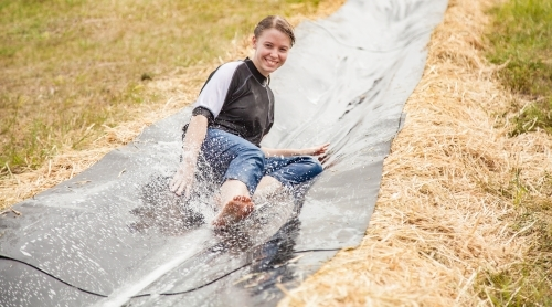 Teen girl sliding down a homemade waterslide laughing