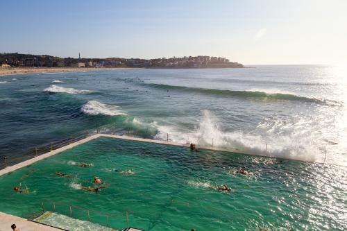 Waves crashing over Bondi Baths at sunrise with people swimming laps