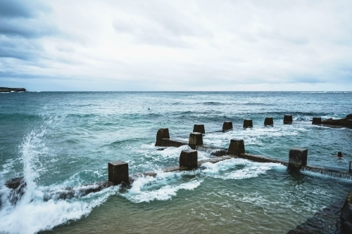 Waves splashing against ocean rock pool in Coogee Sydney on a cloudy day