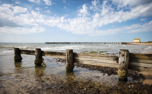 weathered wooden groyne with pier and shed in background