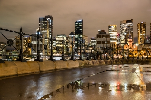 Wet Circular Quay at night after the rain with reflections of buildings along the foreshore path.
