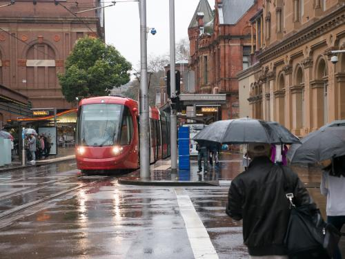 Wet city scene with a tram and pedestrians with umbrellas