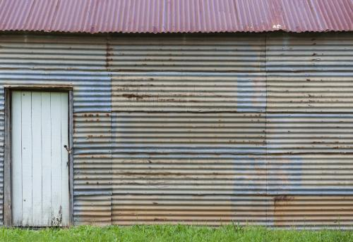 White door set in rusty wall of corrugated iron shed