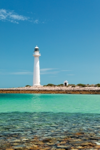 white lighthouse with blue sky and turquoise shallow water