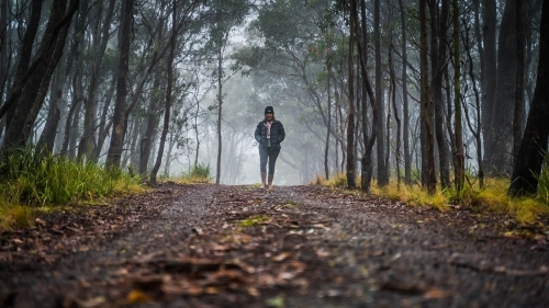 Wide shot of woman walking towards camera on foggy mountain track