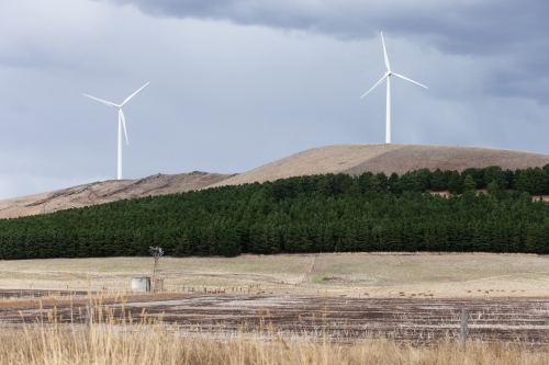 Wind turbines with windmill and paddocks in foreground