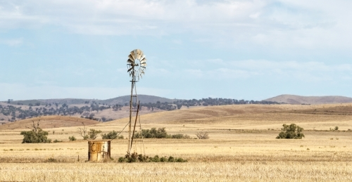 Windmill and old tank in stubble with rolling hills