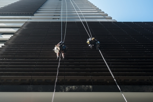 Window cleaners suspended by ropes on hi-rise office building