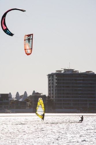 Windsurfing and kitesurfing at a river in a city
