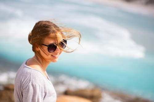 Windswept young woman at beach with hair blowing in the wind