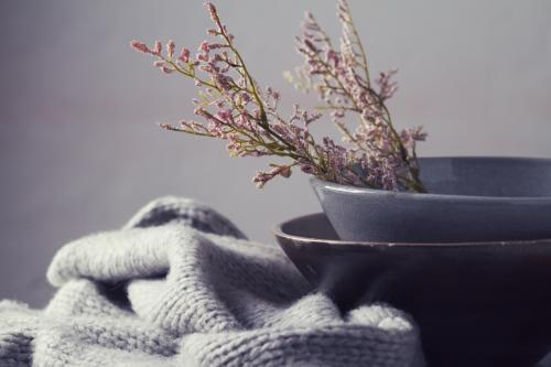 Winter still life flowers grey bowls and knitted scarf horizontal