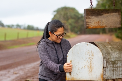 Woman collecting mail from roadside mailbox