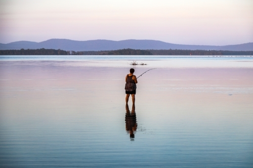 Woman fishing in lake with reflection in water