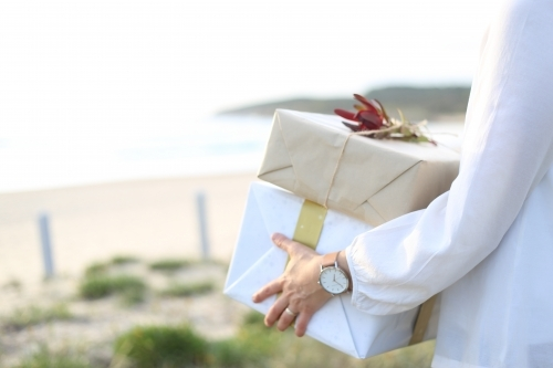 Woman holding presents with beach in background