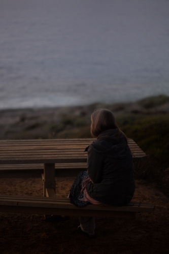 Woman in coat sitting looking out to sea in the dark