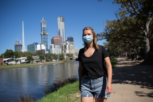 Woman in Face Mask Walking by the Yarra
