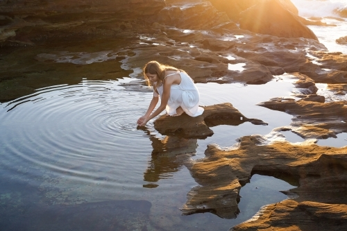 Woman kneeling beside rockpool with golden light and ripples