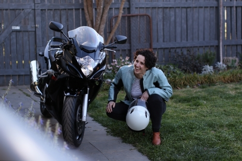 Woman laughing and crouching next to motorbike in garden