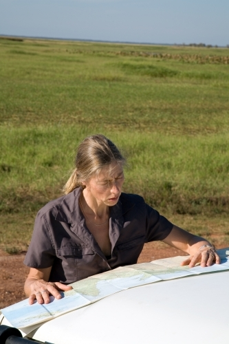 Woman leaning of the bonnet of her car in rural area, reading a map