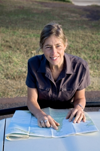 Woman leaning on bonnet of car with map, smiling at the camera