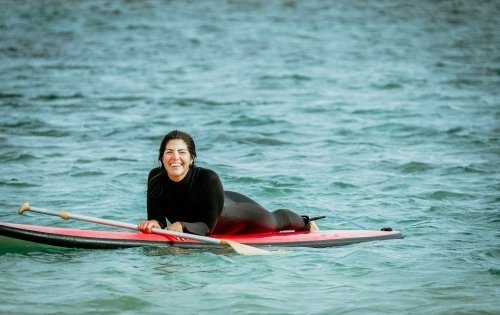 Woman lies on paddle board smiling.