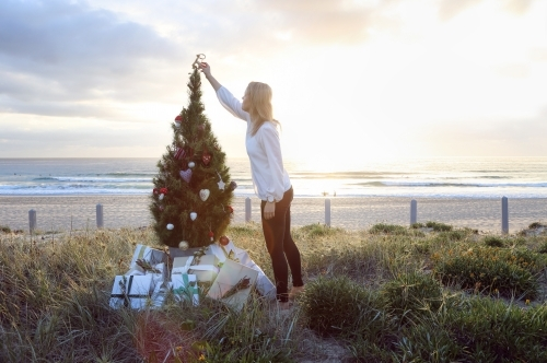 Woman placing decoration on top of Christmas tree on beach at sunrise
