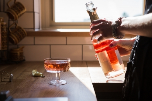 Woman pouring a glass of pink champagne cloe up